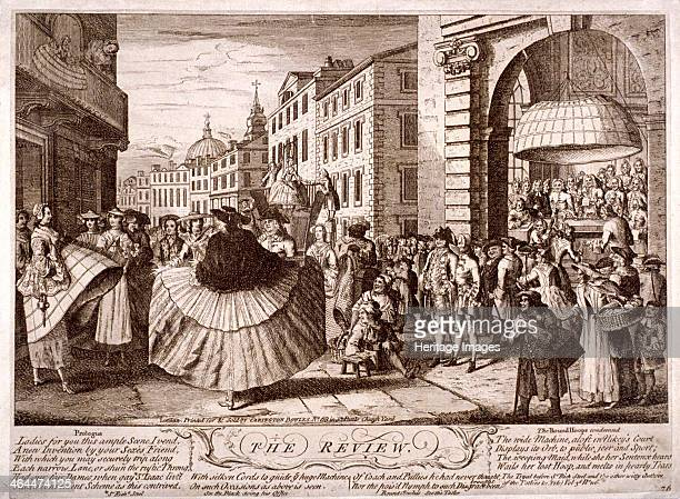 'The review ' 1750 a street in the Soho area London with women of fashion wearing enormous hoop skirts with pulley operated lifting devices in the...