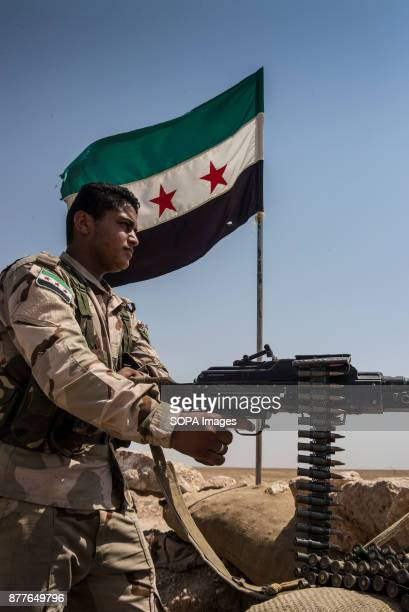 The revoluntionary flag of a Free Syria flies overhead as a young soldier of Quwat al Nukhba overlooks a town of ISIS The Islamic state holds several...