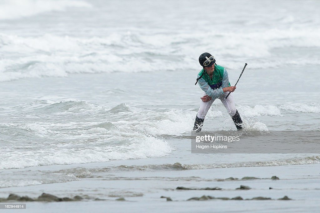 The rider of McCulley retrieves her whip from the sea after taking a fall in the Tinui Highweight Handicap Open during the Castlepoint Beach Races at Castlepoint Beach on March 2, 2013 in Masterton, New Zealand.