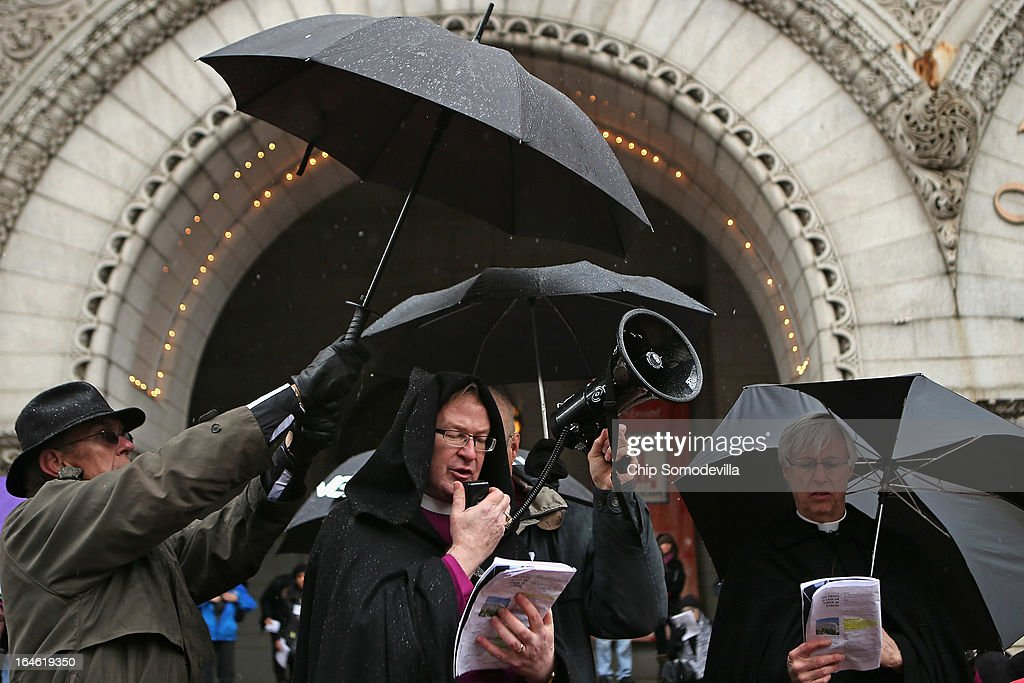 The Right Reverend Shannon S. Johnston (C), bishop of the Episcopal Diocese of Virginia, takes shelter from the rain while leading prayers during the Stations of the Cross march and anti-violence demonstration March 25, 2013 in Washington, DC. About 20 Episcopal bishops from throughout the church lead about 100 clergy and lay people in praying the Stations of the Cross as they processed along Pennsylvania Avenue from the White House to the U. S. Capitol. The march was organized 'to challenge violence, especially the epidemic of gun violence that claims so many thousands of American lives each year.'