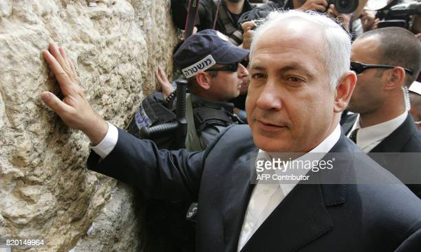 The rightwing Likud leader and former premier Benjamin Netanyahu is surrounded by Israeli security and press as he prays at Western Wall Judaism's...
