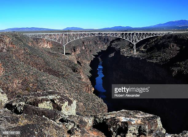 The Rio Grande Gorge Bridge a steel deck arch bridge completed in 1965 spans the Rio Grande Gorge carved by the Rio Grande River near Taos New Mexico...