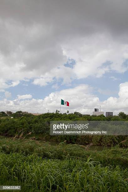 The Rio Grande River flowing through downtown Brownsville looking west with Matamoros Mexico on the left The border wall is being built in sections...