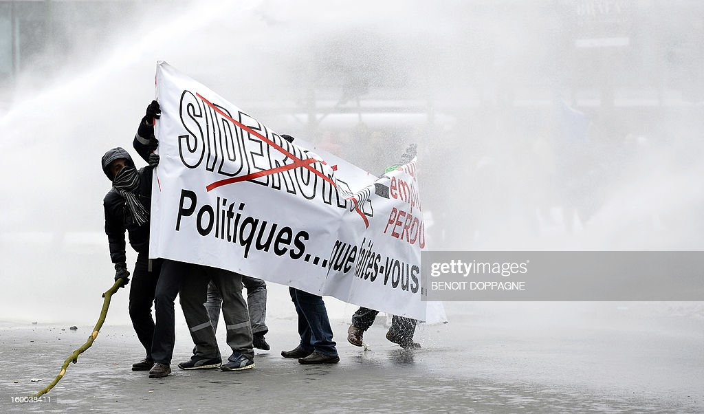 The riot police uses a watercanon to disperse workers of ArcelorMittal holding a protest on the sideline of a meeting between the Federal Government, the Walloon Government and ArcelorMittal unions, on January 25, 2013 near the Prime Minister's residence in Brussels. Yesterday steelmaker ArcelorMittal announced the closure of the cold lines in Liege. 1300 jobs are threatened.