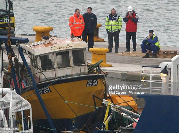 The Rising Sun fishing boat sits on board the Granuaile salvage ship Monday February 6 2006 as Garda officers and dock workers watch it enter...