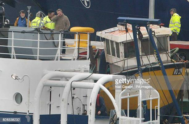 The Rising Sun fishing boat sits on board the Granuaile salvage ship Monday February 6 2006 as relatives of the crew and dock workers watch it enter...
