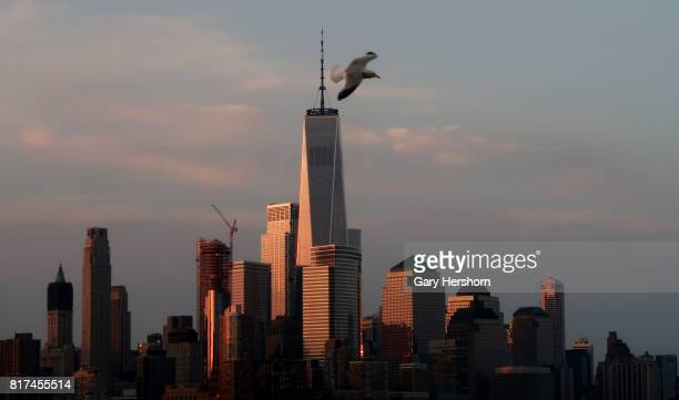 The rising sun illuminates the skyline of lower Manhattan and One World Trade Center in New York City on July 17 2017 as seen from Hoboken New Jersey