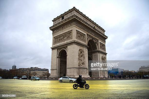 TOPSHOT The road is painted in yellow by Greenpeace activists around the Etoile square in front of the Arc de Triomphe in Paris on December 11 2015 /...