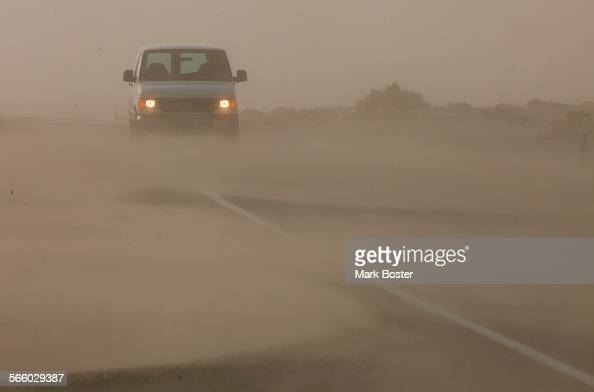 The roadway along old highway 136 heading to Keeler California is obscured by drifting dust from the sandunes next to Owens Lake during a dust storm...
