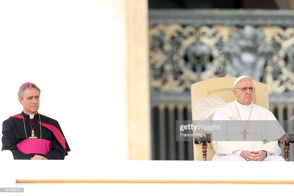 The robes of <a gi-track='captionPersonalityLinkClicked' href=/galleries/search?phrase=Pope+Francis&family=editorial&specificpeople=2499404 ng-click='$event.stopPropagation()'>Pope Francis</a> (R) are blown over his head by a gust of wind as he attends his Weekly Audience, flanked by Prefect of the Pontifical House and personal secretary Georg Ganswein (L) in St. Peter's Square on May 1, 2013 in Vatican City, Vatican. Marking the feast of St Joseph the Worker and World Labor Day today, the Pontiff launched an urgent appeal to Christians and men and women of goodwill worldwide to take decisive steps to end slave labor.