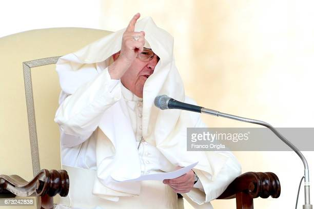 The robes of Pope Francis are blown over his head by a gust of wind as he holds his homily during the weekly audience in St Peter's Square on April...