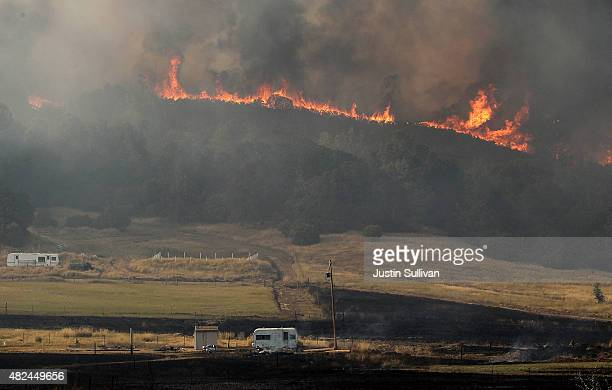 The Rocky Fire burns on a ridge above a ranch on July 30 2015 in Lower Lake California Over 600 firefighters are battling the Rocky Fire that erupted...