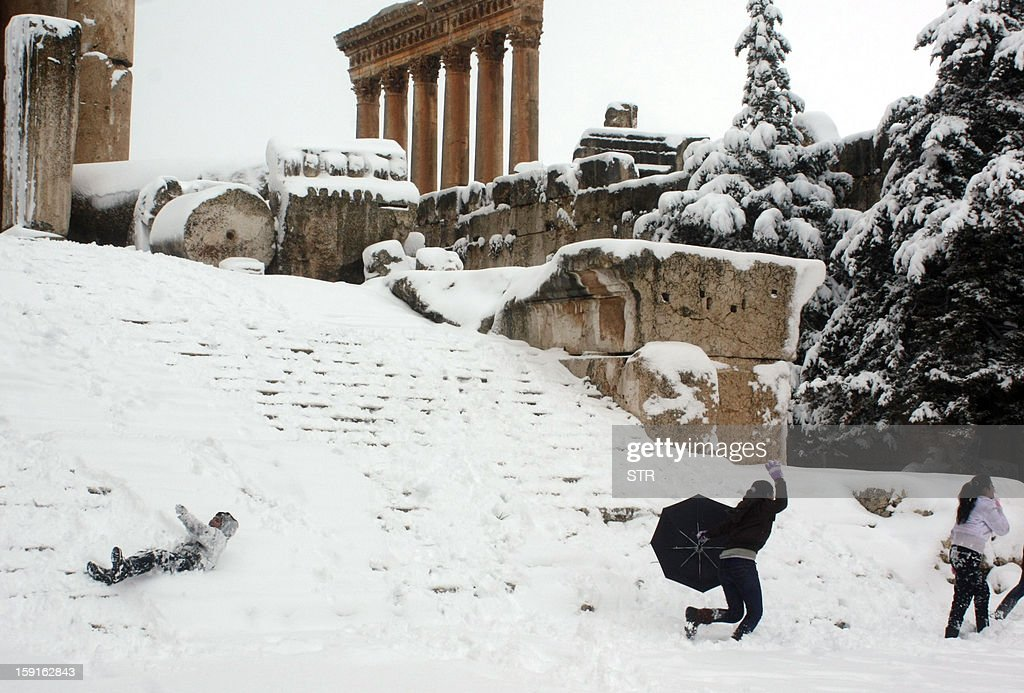 The Roman temple of Jupiter is seen in the background as Lebanese youths play in the snow on January 9, 2013 amid the historic ruins of the ancient town of Baalbek in eastern Lebanon's Bekaa Valley, following a fierce storm which has whipped the region this week with temperatures dropping dramatically and snow falling on low levels across Lebanon, Syria, Jordan and Israel. AFP PHOTO/STR
