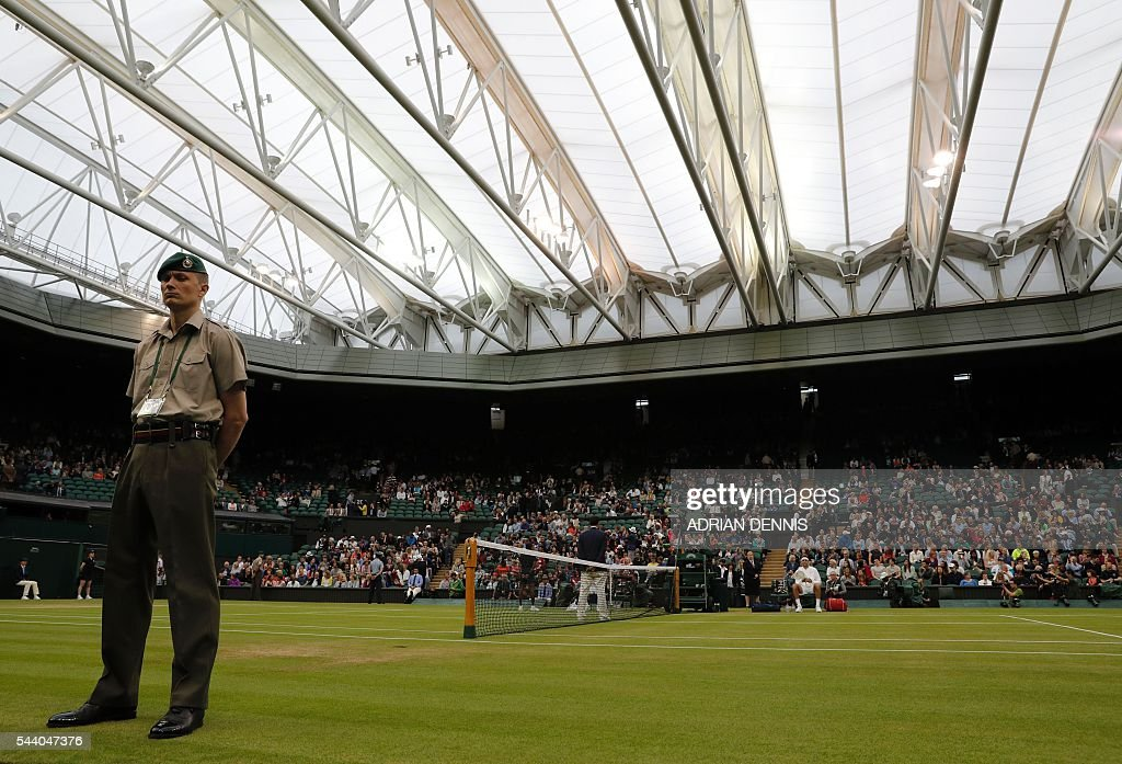 The roof covers centre court as Switzerland's Stan Wawrinka prepares to play Argentina's Juan Martin del Potro in their men's singles second round match on the fifth day of the 2016 Wimbledon Championships at The All England Lawn Tennis Club in Wimbledon, southwest London, on July 1, 2016. / AFP / ADRIAN