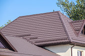 Brown corrugated metal profile roof. The roof of corrugated sheet. Roofing of metal profile wavy shape.