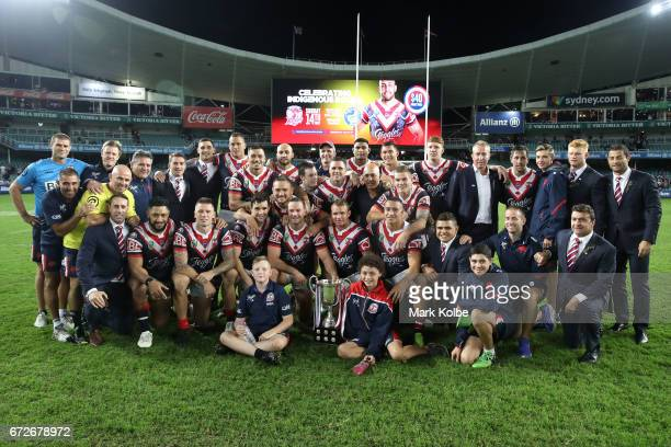 The Roosters team and support staff pose with the Anzac Day trophy after victory during the round eight NRL match between the Sydney Roosters and the...