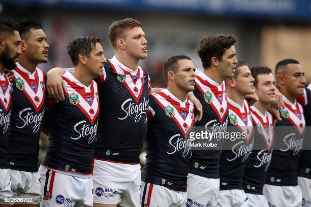 The Roosters team sing the Australian national anthem during the Anzac Day ceremony before the round eight NRL match between the Sydney Roosters and...