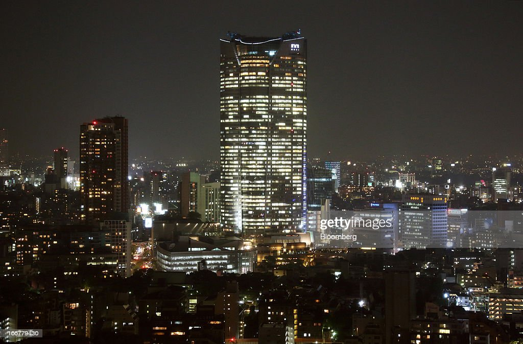 The Roppongi Hills Mori Tower, operated by Mori Building Co., center, stands at night in Tokyo, Japan, on Tuesday, April 17, 2013. While financial firms have cut staff in Japan, technology companies have boosted hiring, and as bankers vacated offices at Roppongi Hills, companies including Google Inc. and Lenovo Group Ltd. moved in. As early as this month, Apple Inc. will also make the complex its home in Japan, two people familiar with the plan said in January. Photographer: Tomohiro Ohsumi/Bloomberg via Getty Images