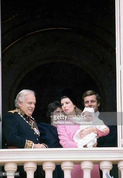 The Royal Grimaldi Family of Monaco stands on a balcony during Monaco's National Day Prince Rainier III Princess Stephanie Princess Caroline holding...
