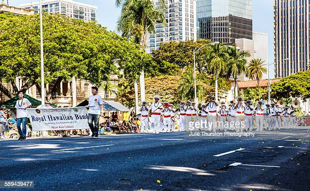 The Royal Hawaiian Band in white uniforms with red and gold sashes marching and playing in the local downtown annual King Kamehameha Day Parade in...
