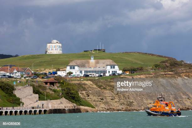 The Royal National Lifeboat Institution RNLI Dover Life boat arrives into Folkestone near the Folkestone is an Art School banner attached to...