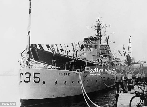 The Royal Navy light cruiser HMS Belfast lying alongside Harumi Pier Tokyo 14th June 1961 The ship is dressed overall with International maritime...