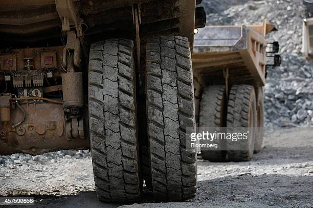 The rubber tires of Caterpillar Inc trucks move across the pit floor as they collect rock ore at the Kibali gold mine operated by Randgold Resources...