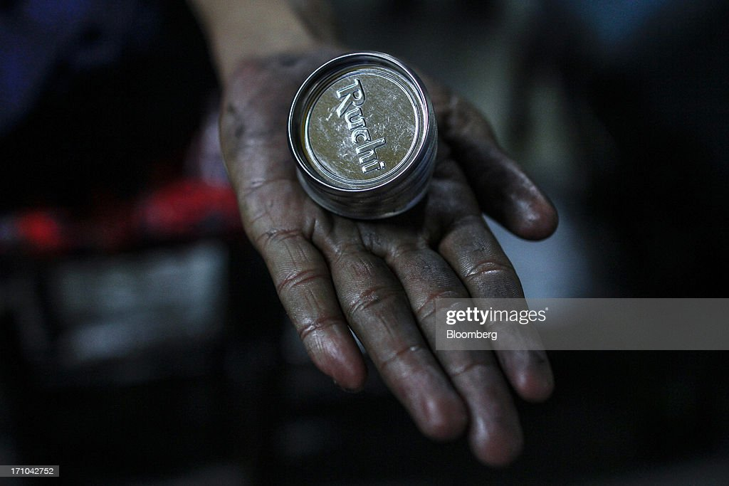 The Ruchi Soya Industries Ltd. logo sits on a tin cap displayed by an employee at the company's edible oil refinery plant in Patalganga, India, on Tuesday, June 18, 2013. Monsoon, which accounts for 70 percent of Indias annual rainfall, covered the entire country in a record time, accelerating plantings of crops from rice to soybeans and cotton. Rains covered the whole of India by June 16, the earliest ever and ahead of the normal date of July 15, said D.S. Pai, head of the long-range forecasting division at the India Meteorological Department. Photographer: Dhiraj Singh/Bloomberg via Getty Images