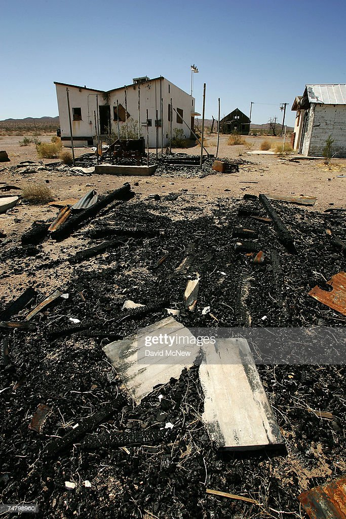 The ruins of a burned building lie behind a destroyed cafe along old Route 66 on June 16, 2007 in Ludlow, California. Route 66 opened in 1926 to become an icon of American motoring freedom. It stretched from Chicago to Los Angeles and became a western migration route for people looking for work during the great depression of the 1930s or to escape the Dust Bowl disaster. Later it offered vacation getaways and driving adventures until 1985 when it was decommissioned as a federal highway. Today the motels, gas stations, and roadside attractions along the 'Mother Road' are disappearing at an alarming rate. Route 66 aficionados try to preserve some reminders of the by-gone era ? restoring some buildings, collecting memorabilia, and erecting thousands of new signs that read 'Route 66' - but most of the old landmarks are already in a state of decay or destroyed by vandals and neglect. Freeways, modern hotel chains, developer's projects, and even tourist attractions are blotting out the original reminders of the highway that inspired countless movies, books, and songs about life on the Western highway. Last week the National Trust for Historic Preservation included the old motels of Route 66 on its list of the 11 most endangered historic places.