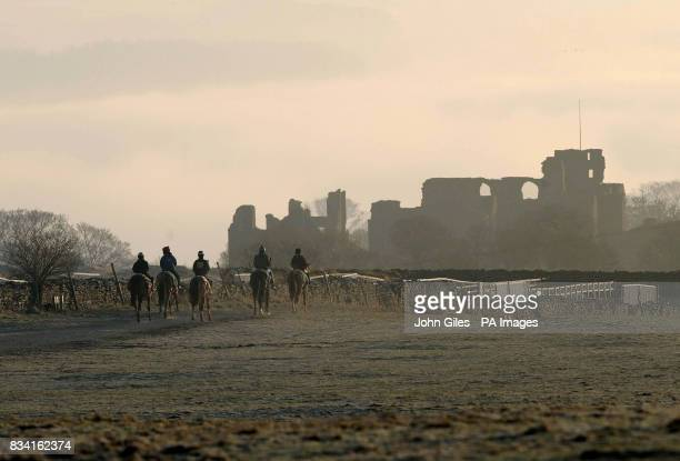 The ruins of Middleham Castle stand above the fog as racehorse strings make their way onto the gallops above Middleham North Yorkshire