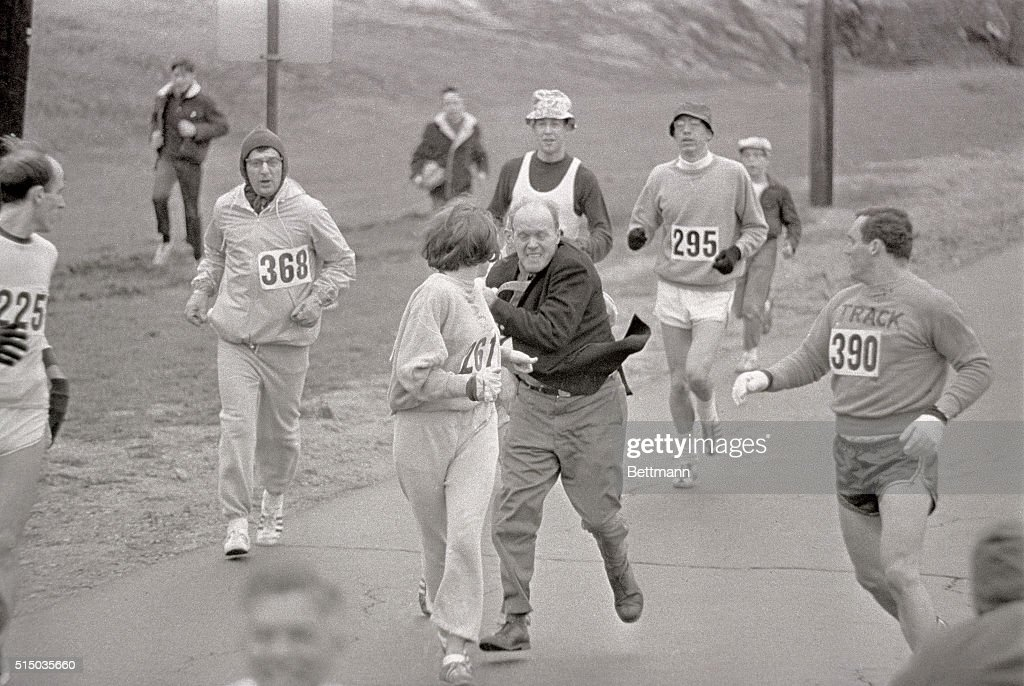 The rule that no women shall run in the Boston Athletic Association (BAA) Marathon is being put to a very real test in this photo. Trainer Jack Semple (in street clothes) enters the field of runners to try to pull Kathy Switzer (261) out of the race. Male runners move in to form protective curtain around the female track hopeful, until the protesting trainer is finally wedged out of the race, and the lady is allowed to finish the marathon.