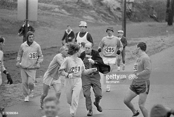 The rule that no women shall run in the Boston Athletic Association Marathon is being put to a very real test in this photo Trainer Jack Semple...