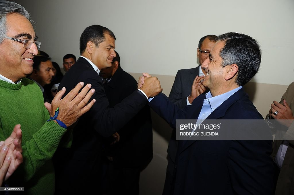 The ruling party's candidate for Quito's Mayor's Office, Augusto Barrera (R), is greeted by Ecuadorean President Rafael Correa (C) after casting his vote at a polling station in Quito, as Ecuador holds municipal elections on February 23, 2014.