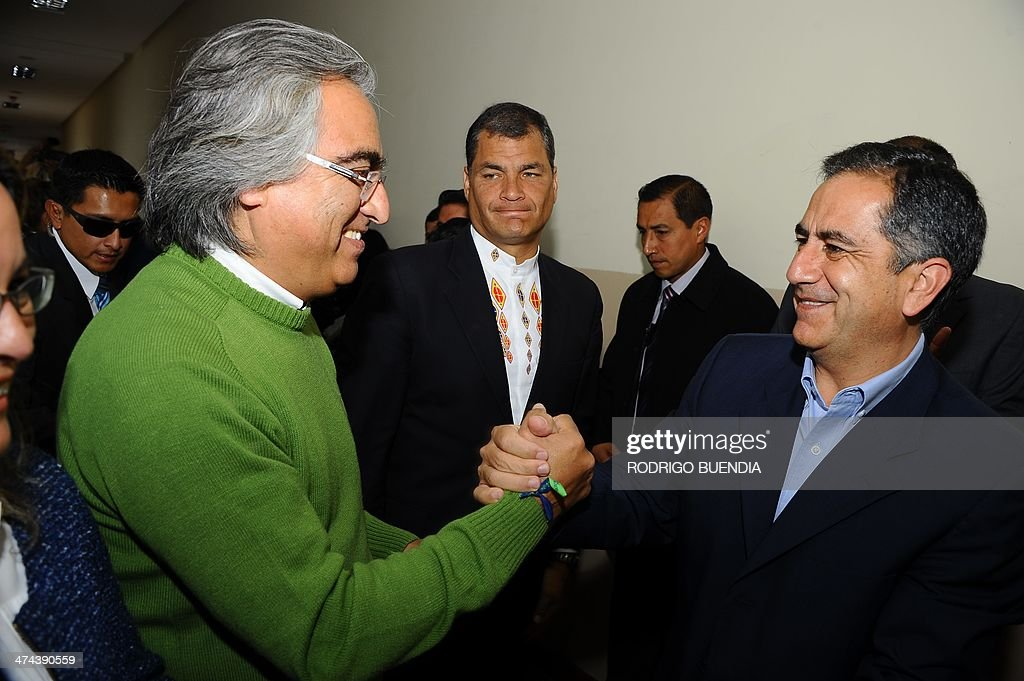 The ruling party's candidate for Quito's Mayor's Office, Augusto Barrera (R), is greeted by the Prefecture of Pichincha Gustavo Baroja who seeks reelection, as Ecuadorean President Rafael Correa (C) looks on, after casting his vote at a polling station in Quito, as Ecuador holds municipal elections on February 23, 2014.