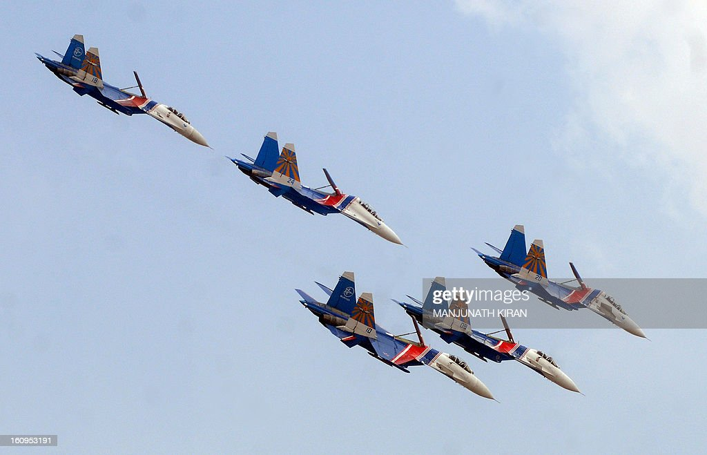 The Russian Airforce aerobatic display team, Russian Knights arrive in formation in their Sukhoi Su-27s on the third day of the 9th edition of the Aero India 2013 at Yelahanka Air Force station in Bangalore on February 8, 2013. India, the world's leading importer of weaponry, opened one of Asia's biggest aviation trade shows February 6 with Western suppliers eyeing lucrative deals and a Chinese delegation attending for the first time. AFP/Manjunath KIRAN