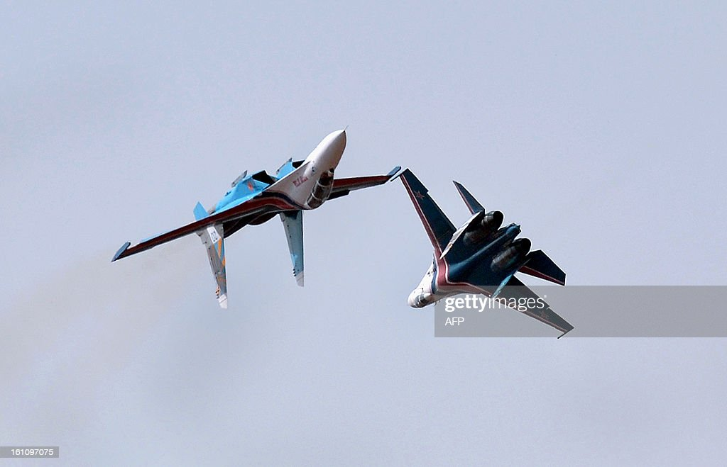 The Russian Knights aerobatic demonstration team fly in their Sukhoi SU-27s on the fourth day of Aero India 2013 at Yelahanka Air Force station in Bangalore on February 9, 2013. India, the world's leading importer of weaponry, opened one of Asia's biggest aviation trade shows February 6 with Western suppliers eyeing lucrative deals and a Chinese delegation attending for the first time. AFP PHOTO/Manjunath KIRAN