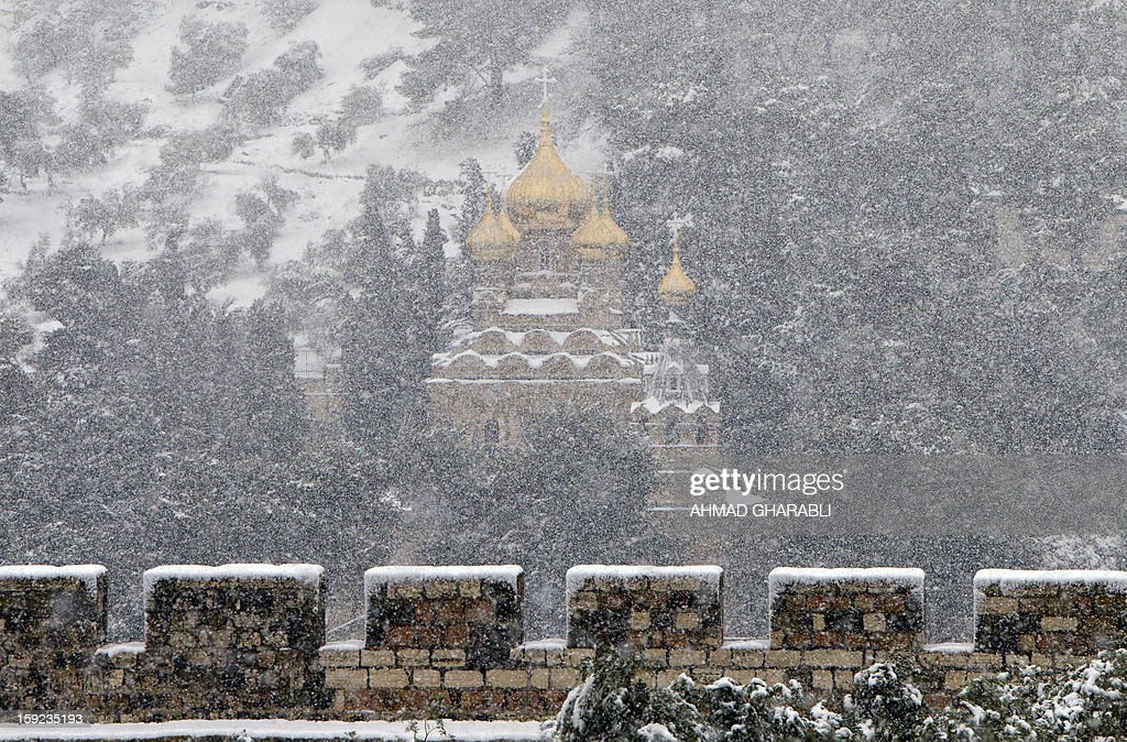 The Russian Orthodox Church on Mount of Olives in Jerusalem's old city is seen as snow fall on January 10, 2013. Jerusalem was transformed into a winter wonderland after heavy overnight snowfall turned the Holy City and much of the region white, bringing hordes of excited children onto the streets. AFP PHOTO/AHMAD GHARABLI