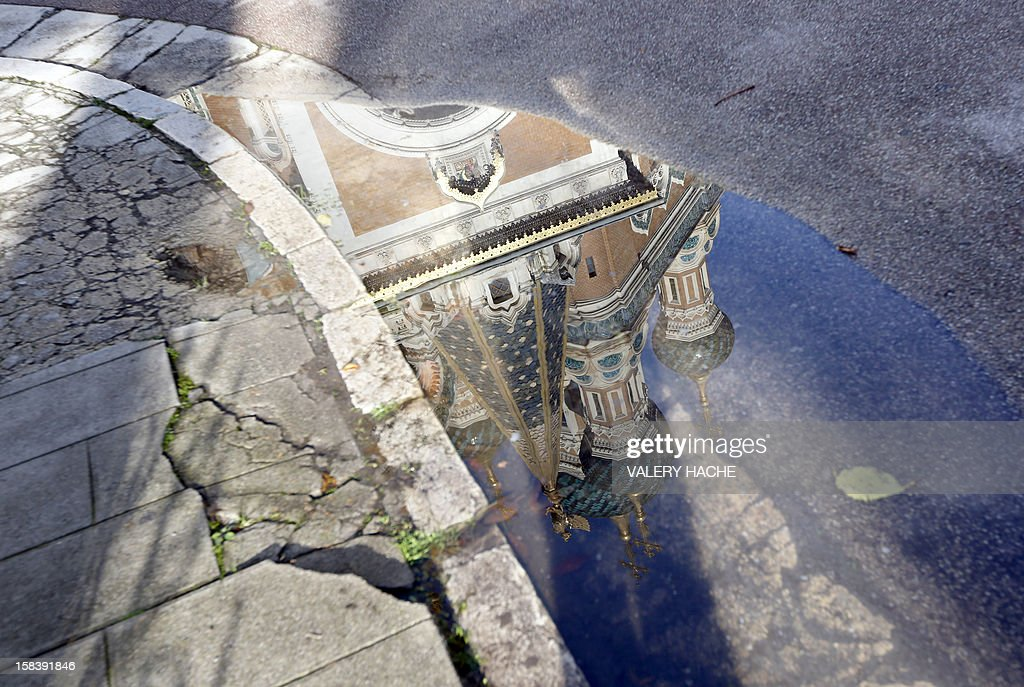 The Russian orthodox church Saint-Nicholas cathedral, which has recently been handed over to the Russian Orthodox Church, reflects itself in a puddle on December 15, 2012, in Nice, southeastern France. The church will celebrate 100th anniversary this week. AFP PHOTO / VALERY HACHE