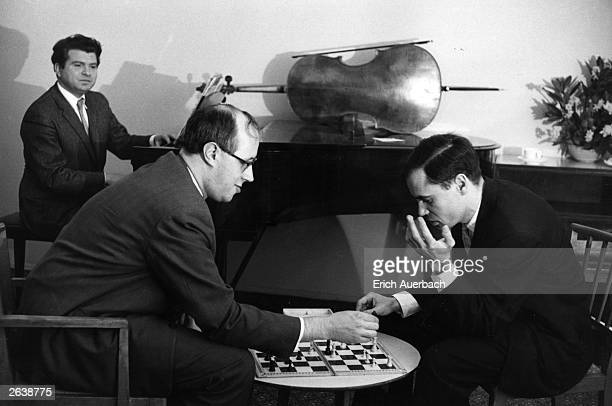 The Russian pianist Emil Gilels is at the piano while Leonid Kogan and the Russian cellist and conductor Mstislav Rostropovich play chess in their...