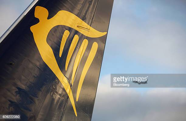 The Ryanair Holdings Plc company logo sits on the tail fin of an aircraft as another aircraft flies beyond at Dublin Airport operated by Dublin...
