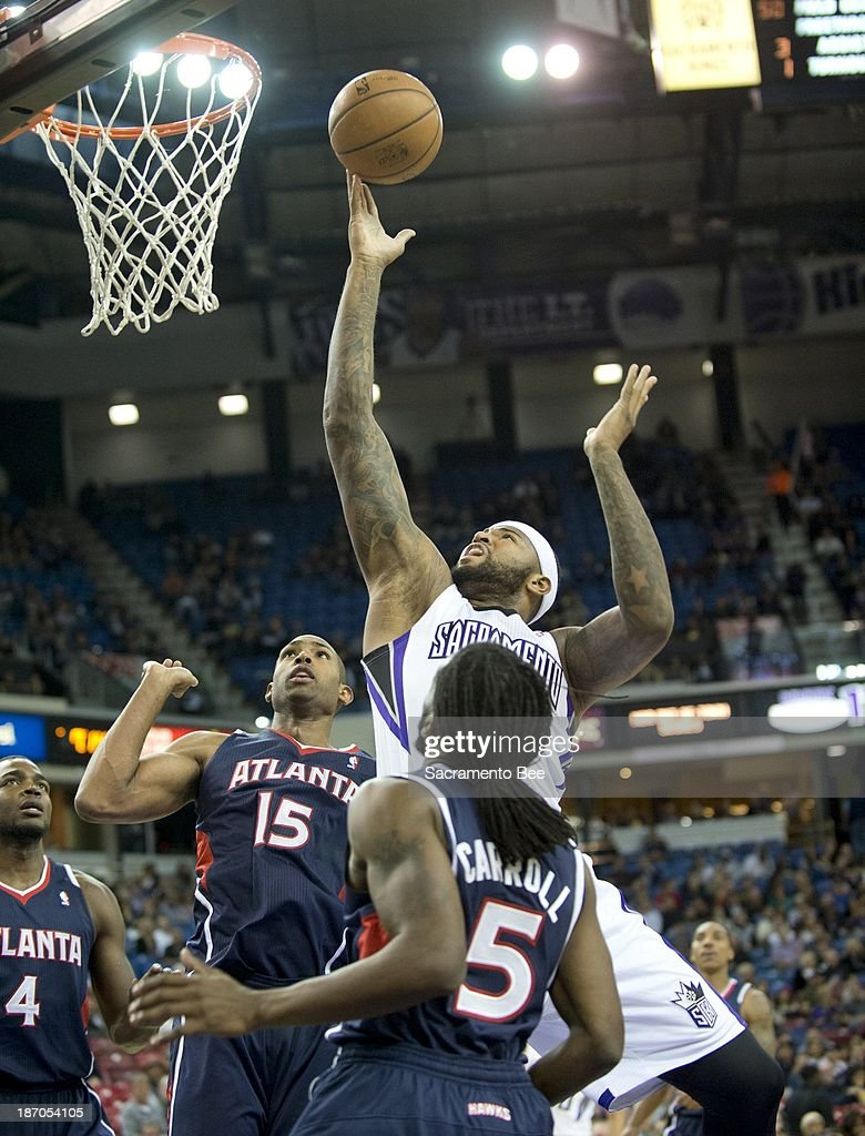 The Sacramento Kings' DeMarcus Cousins, top, scores against the Atlanta Hawks at Sleep Train Arena in Sacramento, California, on Tuesday, November 5, 2013.