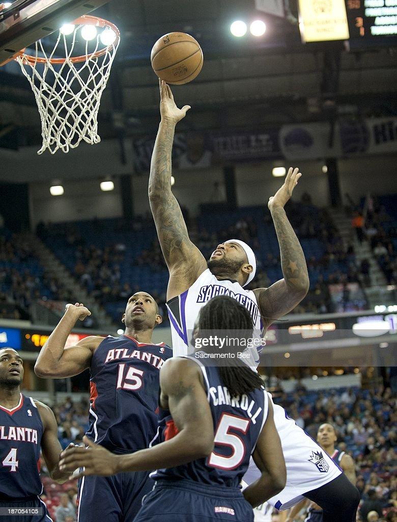 The Sacramento Kings' DeMarcus Cousins, top, scores against the Atlanta Hawks at Sleep Train Arena in Sacramento, California, on Tuesday, November 5, 2013.