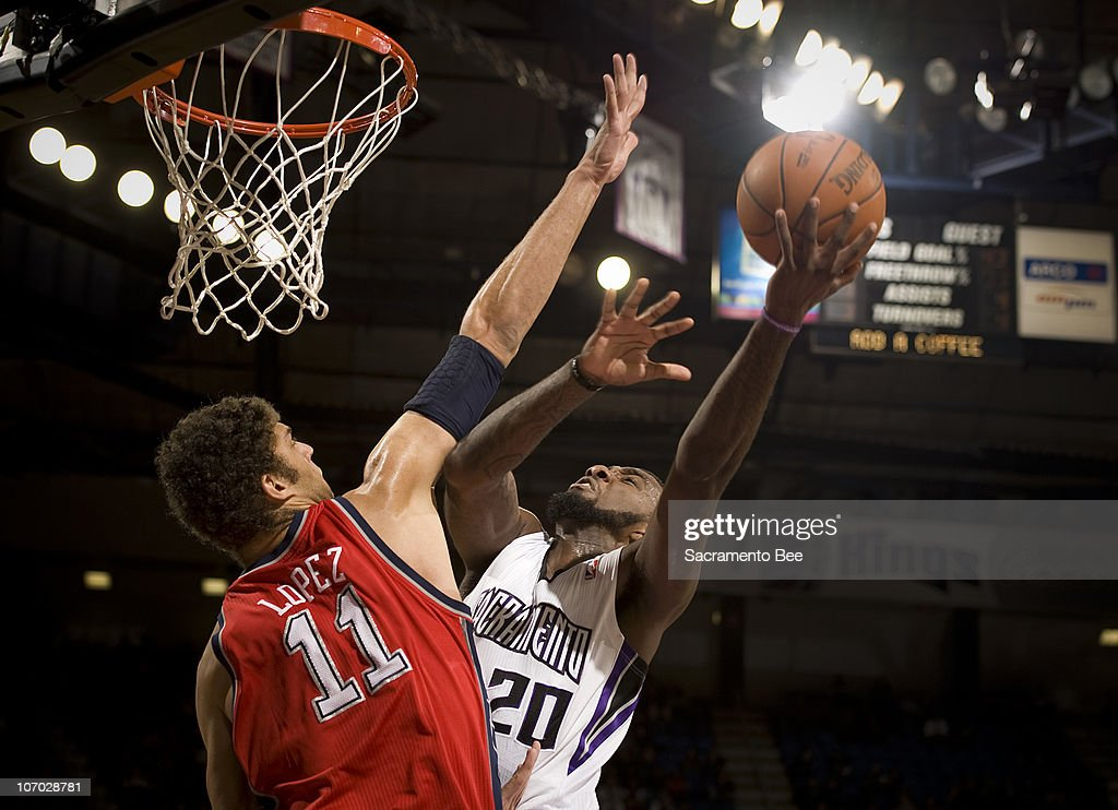 The Sacramento Kings' Donte Greene (20) scores over the New Jersey Nets' Brook Lopez in the first quarter at Arco Arena in Sacramento, California, on Friday, November 19, 2010.