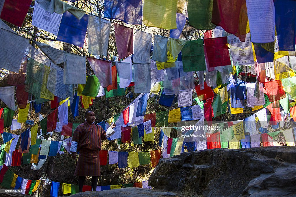 The sacred place Burning Lake with prayer flags and Tsha-tsha, small prayer stones honouring ancestors (mixture of clay and dead ash) and laid down under protecting rock near Burning Lake on November 18, 2012 in Bumthang, Bhutan.