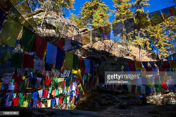 The sacred place Burning Lake with prayer flags and Tshatsha small prayer stones honouring ancestors and laid down under protecting rock near Burning...