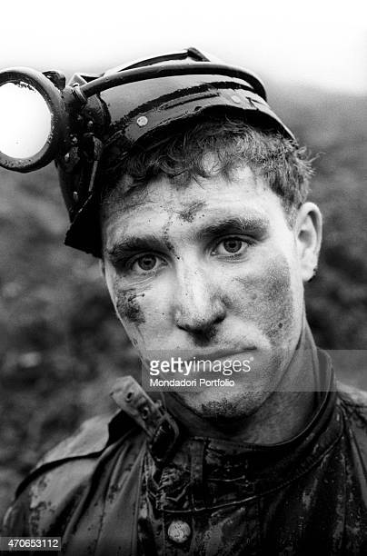 'The sad gaze of a young miner who has been provided with a helmet with his face covered with mud who has just lost his little brother in the...