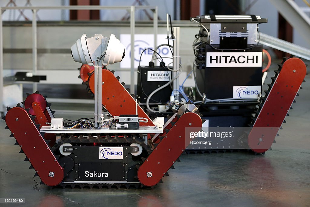 The Sakura, left, and Tsubaki remote-controlled transfer robots, developed by Chiba Institute of Technology's (CIT) Future Robotics Technology Center (fuRo) in the New Energy and Industrial Technology Development Organization's (NEDO) unmanned anti-disaster system research and development project, stand with Hitachi Ltd.'s gamma camera, top right, during a media review at the university's Shibazono campus in Narashino City, Chiba Prefecture, Japan, on Wednesday, Feb. 20, 2013. NEDO, Japan's largest public R&D management organization, introduced its latest disaster response robot technologies today. Photographer: Kiyoshi Ota/Bloomberg via Getty Images