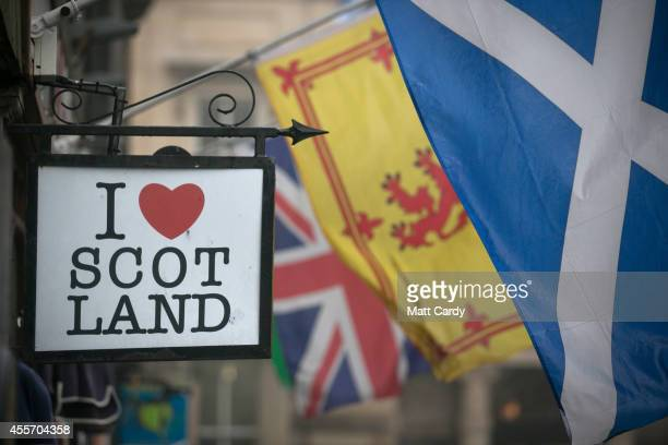 The Saltire flag flies next to the Royal Standard of Scotland and the Union Flag above a gift shop in central Edinburgh on September 19 2014 in...