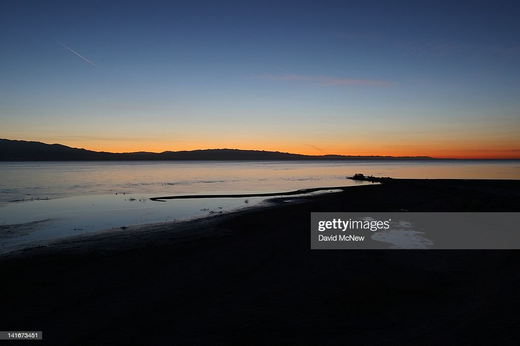 The Salton Sea is seen before dawn in an area where a controversial development would create a new town for nearly 40,000 people on the northwest shore of the biggest lake in California, the Salton Sea, on March 21, 2012 south of Mecca, California. The Center for Biological Diversity and the Sierra Club have filed a lawsuit against Riverside County after the Board of Supervisors approved a record-sized development project for Riverside County, saying that it would increase pollution and threaten wildlife in nearby parks at the Salton Sea and in the largest state park in California, Anza-Borrego Desert State Park. Though massive fish die-offs occur annually, drawings in the Travertine Point plans feature peaceful marinas but the lake has been plagued by dropping water levels and increasing salt levels for decades. Scientists say that a catastrophic decline in the fish population is inevitable and a resulting 25 to 50 percent drop in the migratory bird population will destroy a major stopping point in the Pacific bird migration route. The shrinking salt lake is exposing more and more fine dust, posing health problem as blows it across the region. Funding to stop the ecological collapse of the sea is not likely in the near futures with its $9 billion price tag.