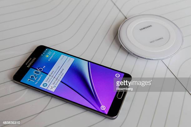 The Samsung Electronics Co Galaxy S6 Edge Plus smartphone left and Fast Charging wireless pad are displayed during the Samsung Unpacked 2015 event in...